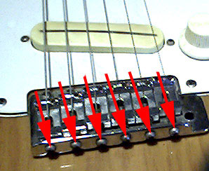 The guitar intonation adjustment screws as found on some brands and models of electric guitars